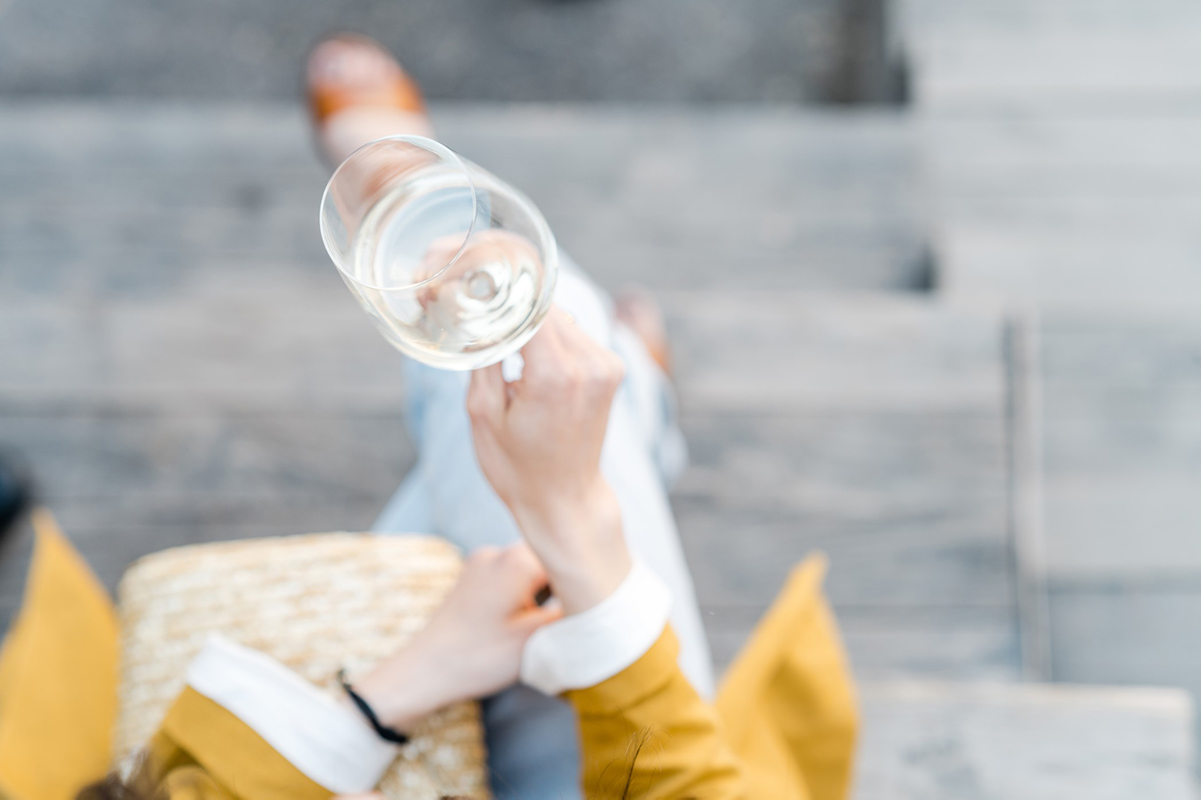 Woman enjoying a glass of Sauvignon blanc outdoors