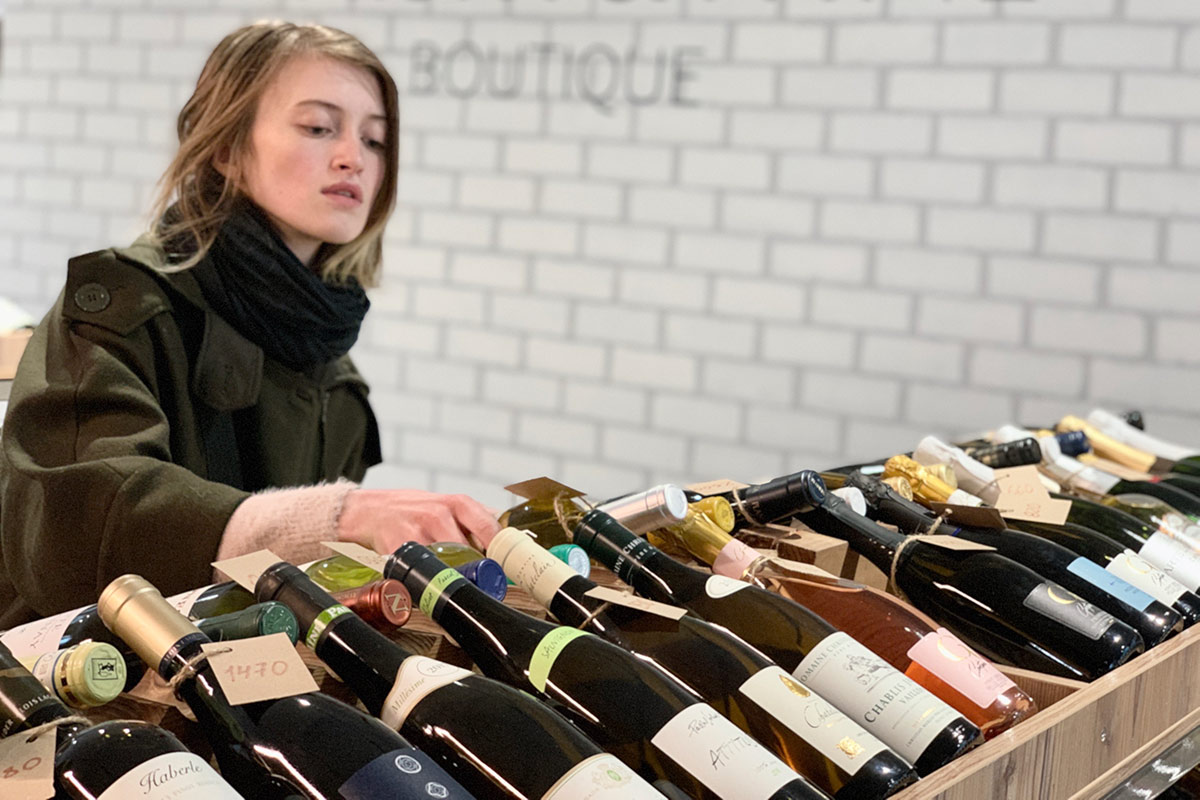 Woman deciding which wine to buy