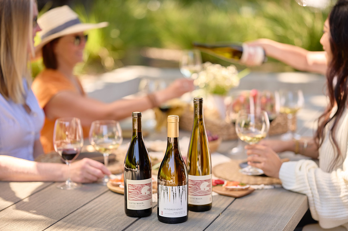 Friends enjoying wine at a picnic table.