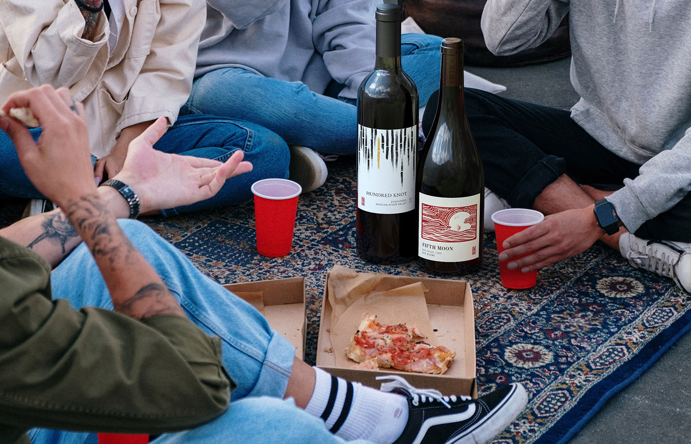 Friends enjoying pizza and wine together.
