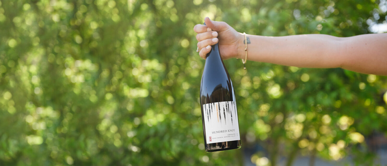 Hand holding RD Winery Hundred Knot Grenache in front of bushes.
