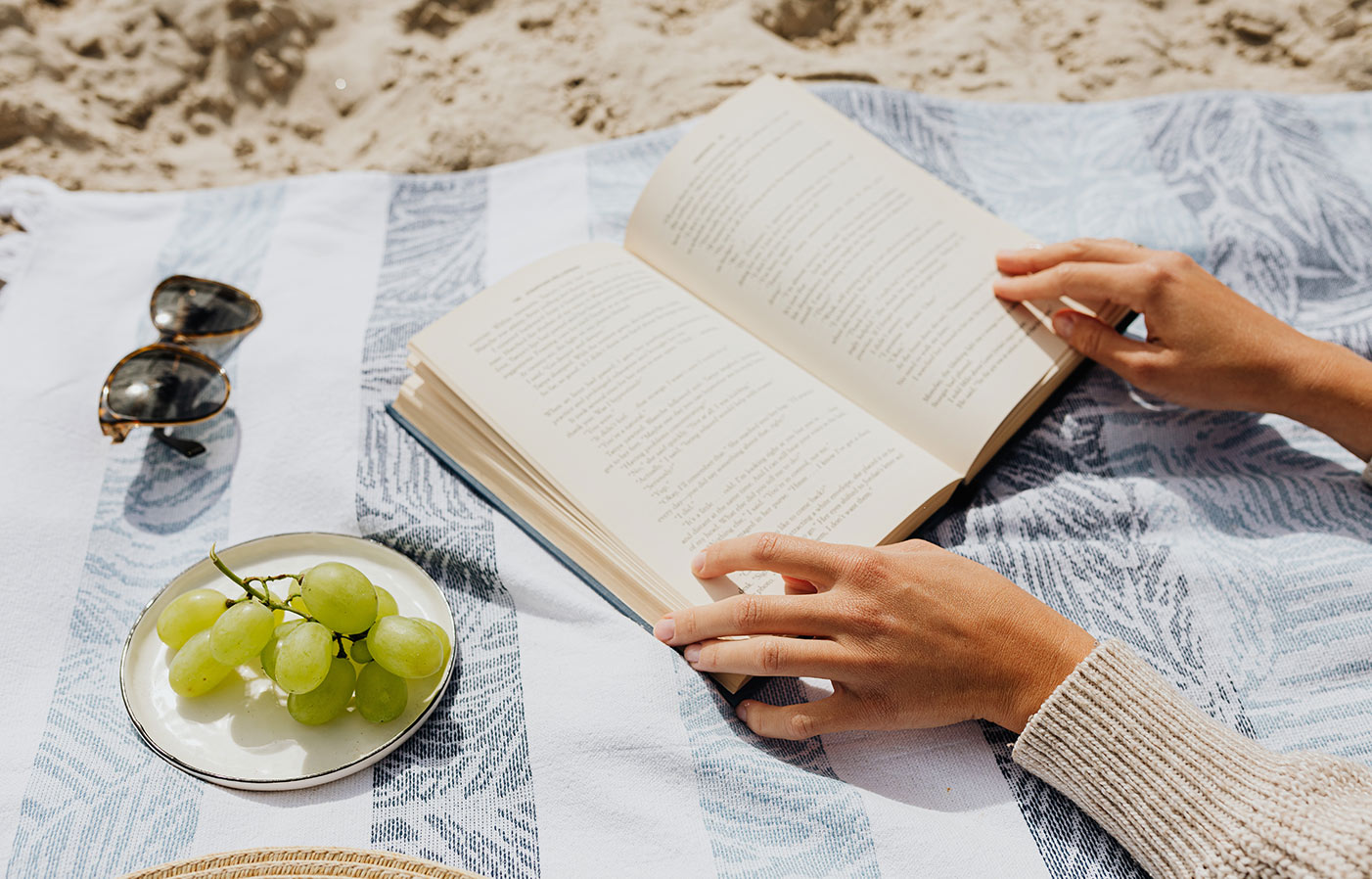 Woman reading a book on the beach with grapes.