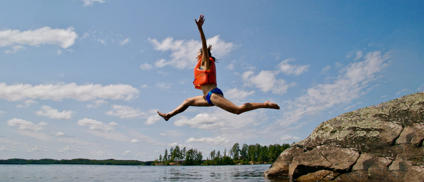 Woman jumping into lake with an orange life vest on.