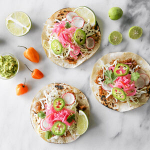 Three fish tacos on a marble surface.