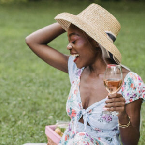 Woman in hat laughing with a glass of rosé in hand
